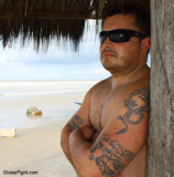 a wet sweaty beach hunk man under cabana.jpg