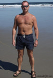 suntanned dad swimming trunks standing beach.jpg