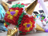 Colorful pinatas are stuffed with candy and the kids have a blast batting them