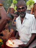 Local priest offering holy fire and ashes to the members of the Mulaipari procession at Koovathupatti, Tamil Nadu.