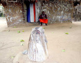 Fetish priest Mensah Gakli and a legba in front of his shrine.