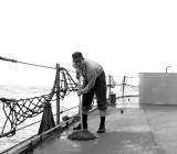 Sailor swabbing deck  on the USS Hugh Purvis, DD 709, in 1962