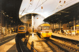 Class 43047 ROTHERHAM ENTERPRISE pulls away from Newcastle, while the rear of 43067 is in the platfom - Nov 1990.