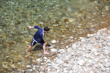 Albanian boy coming wading in the chilly river