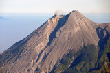 A wisp of smoke rises from the lip of Mt. Merapi