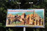 Billboard with the statues from the Airport Roundabout in front of the historic sites of Turkmenistan