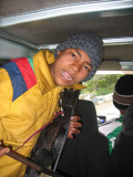 On board entertainment - boy playing a traditional instrument called a Kutumba
