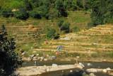 Terraced fields on laundry day along a river, Nepal