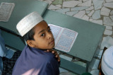 Bangladeshi boy looking up from his desk, Dhaka Medrassa