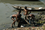 Men digging through the mud on the banks of the Buriganga River, Old Dhaka
