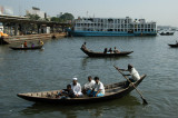 The oarsman uses a single long yuloh to row like a Venetian gondolier while facing forward, Dhaka