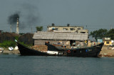 A pair of black wooden freighters in front of a belching smokestack on the outskirts of Dhaka