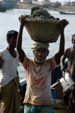 Men carry heavy baskets of sand off the ship