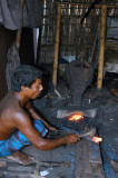 Blacksmith with his forge set up in a hut, Fatulla Market