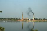 Reflextions of smokestacks in a lake southeast of Dhaka