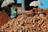 Bangladeshi women breaking old bricks into tiny bits