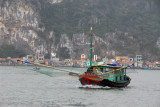 Fishing boat with nets spread leaving Hon Gai