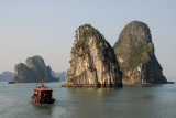 Tourist boat dwarfed by the magestic stone islands, Halong Bay