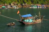 Fishing boat arriving at a floating village, Halong Bay