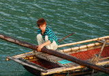 Vietnamese boy with reddish hair in a rowboat, Halong Bay