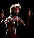 Backlit aboriginal busker with clapsticks