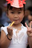 Little Vietnamese girl eating chip