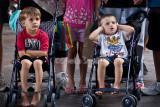 Two little boys in crowd watching busker