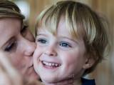 Smiling little boy gets kissed
