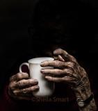 Aged hands hold a mug
