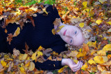 Lying in autumn leaves