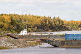 Barges docked in front of fall foliage