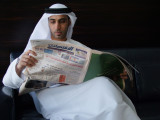 Reading the paper Dubai.jpg