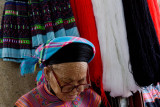 Older woman making traditional clothing at a craft shop in Sapa
