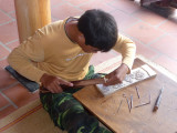 This young man is carving block prints. The Dong Ho style of painting and printing are 300 years old.