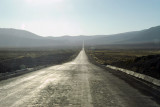 Straight road across the Altiplano headed into the sun
