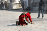 Tibetan pilgrim prostrating in front of the Jokhang, Barkhor Square