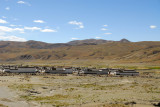 Village of identical Tibetan-style houses on the side of the road