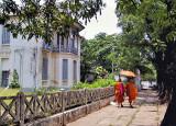 Monks walking past an empty villa