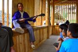 4174 Playing a traditional instrument and entertaining the some of the village youth.