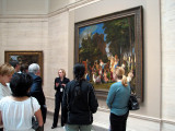 A docent discusses The Feast of the Gods.