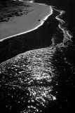 silver sand beside a jewelled sea