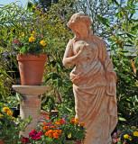 Ceramic maiden enjoying gardens