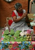 Selling prickly pear cactus leaves (spines removed) and fruit in the market