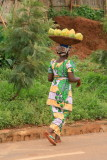 A Rwandan woman wearing colorful traditional clothing carries produce.