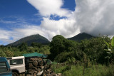 Mt. Muhabura and Mt. Gahinga from the entrance to Mgahinga Gorilla National Park.  Clouds move around the volcanic peaks constantly.