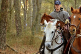 [APRIL 2007] A young saltwater cowboy carries the new foal after it was unable to keep up with the rest of the herd.