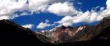 Peaks Tucked Away Under Blue Cloudy Skies