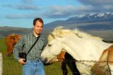 Roy greeting an Icelandic horse with Mount Hekla in the back