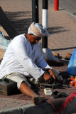 Omani street craftsman outside the souq gates