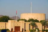 Gate to Nizwa Souq with the massive tower of Nizwa Fort
